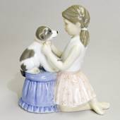 Girl trying bow tie on dog, Royal Copenhagen figurine