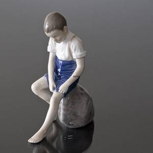 Boy sitting on stone rolling up trousers, Bing & Grondahl figurine No. 1757 | No. B1757 | DPH Trading