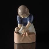 Girl with doll, gently putting it into the basket, Bing & Grondahl figurine...