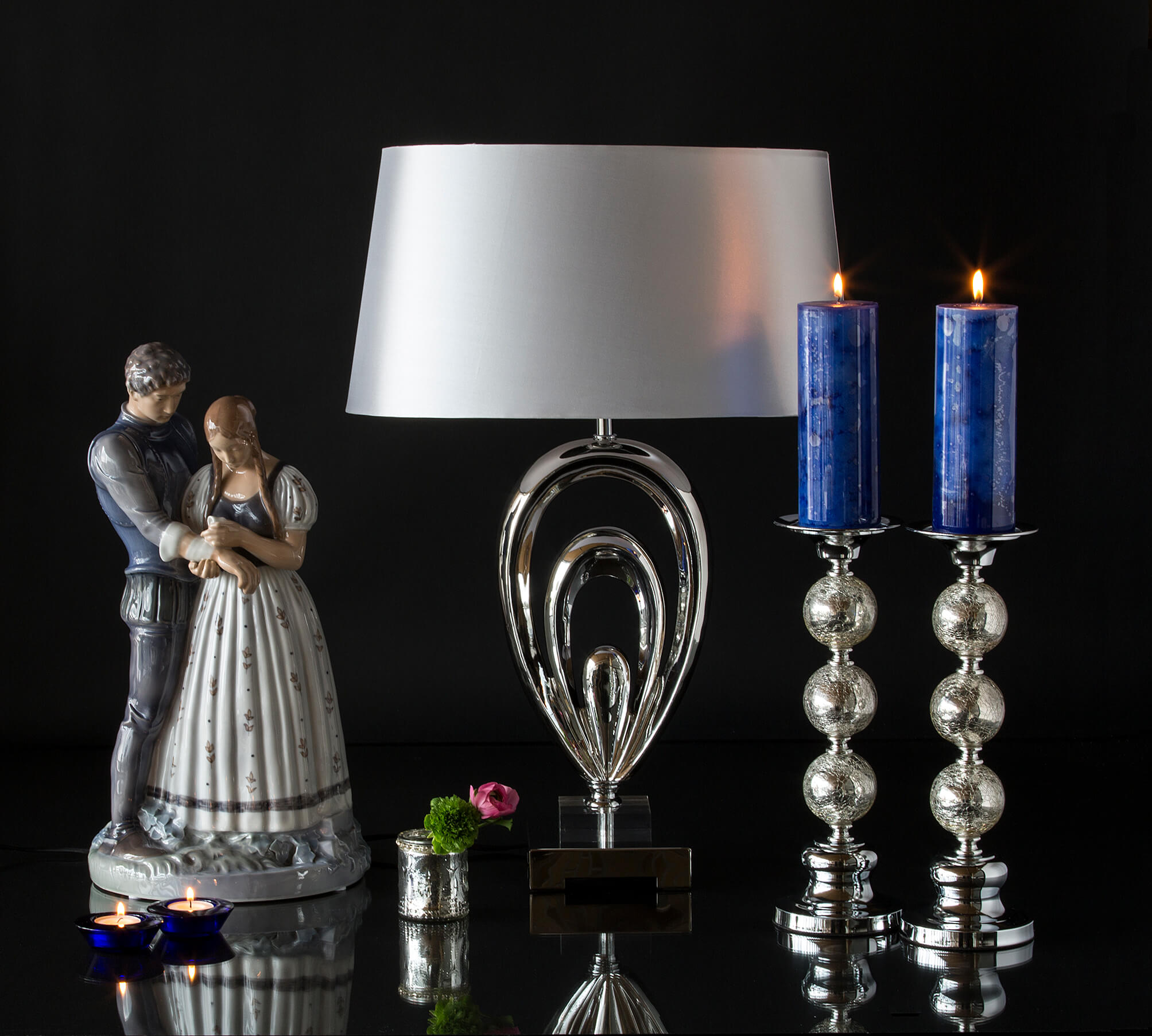 Large Knight and Maiden figurine next to a glass lamp and candlesticks