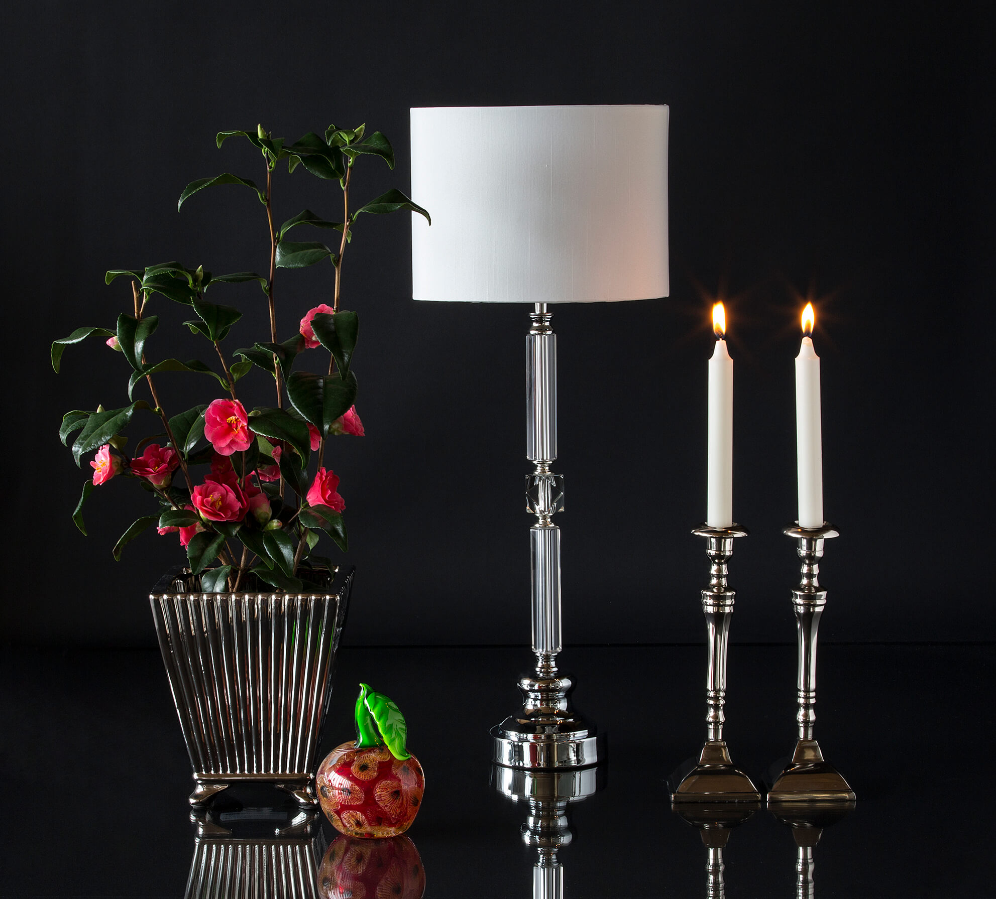 Large metal flower pot with glass apple, tablelamp and candlesticks