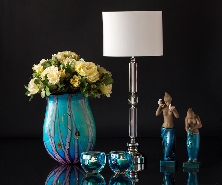 Blue glass vase with tealight candlesticks and lamp with two figurines