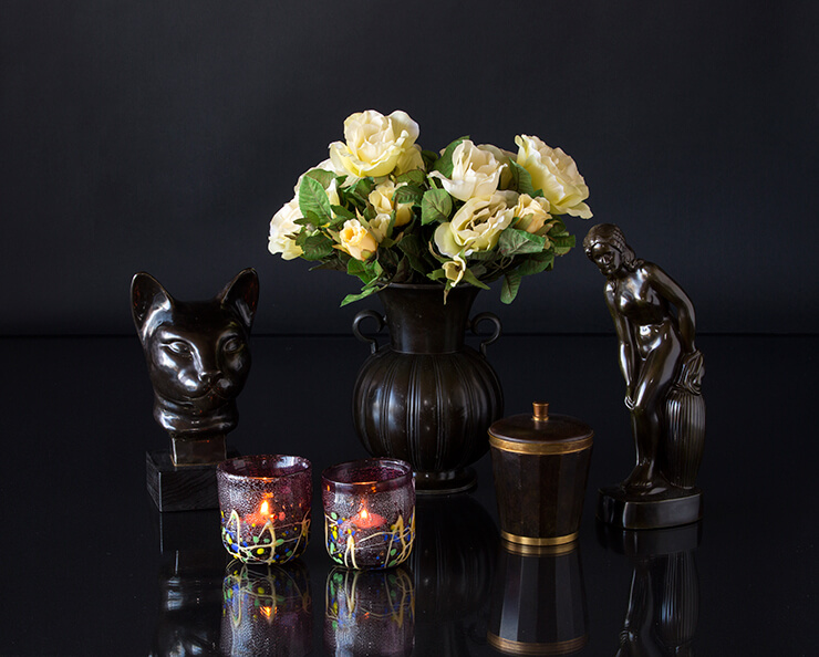 Black figurines of woman and cat's head with black vase and glass tealight candleholders