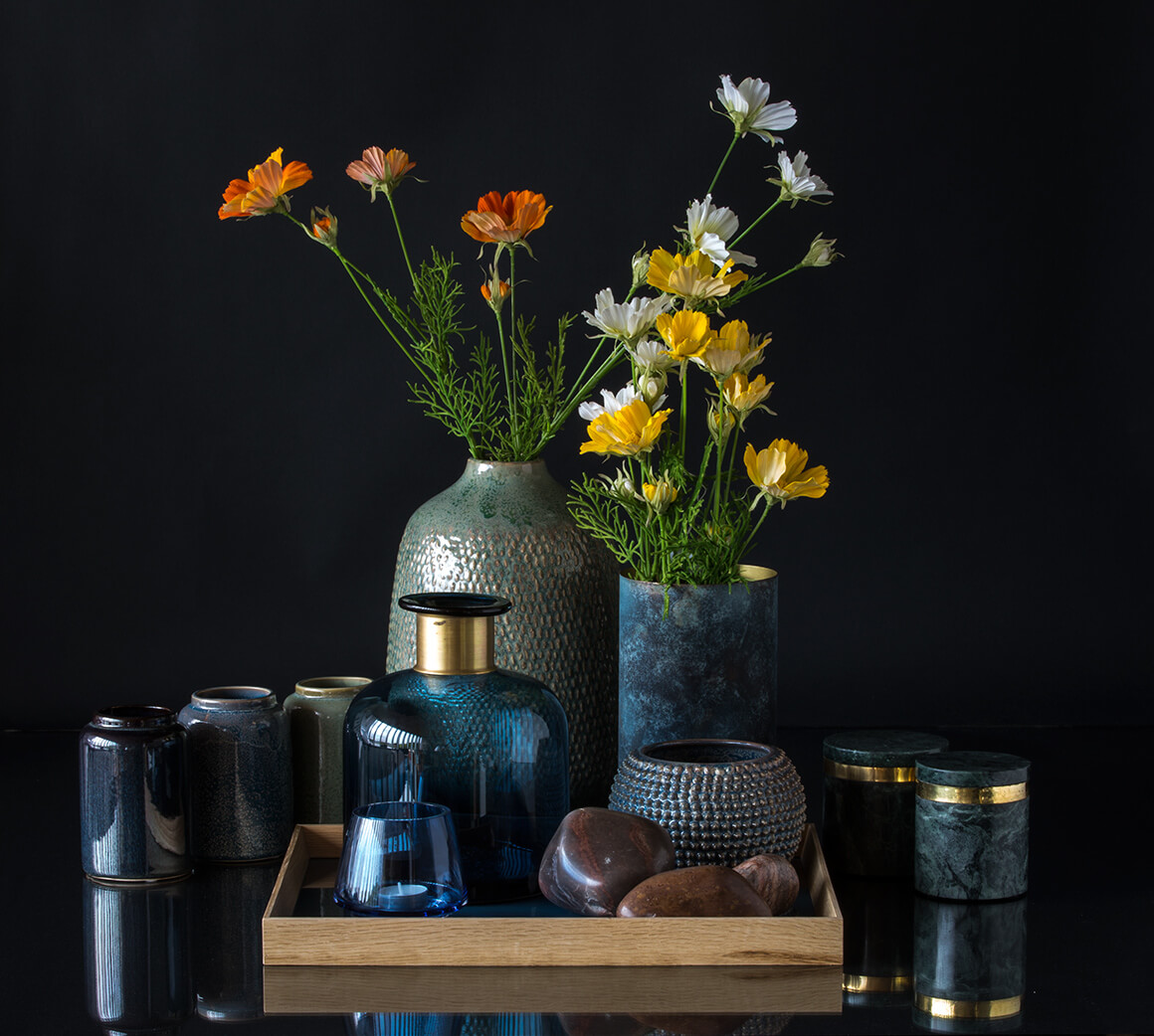 Large vase with blue bottle and small flower pot on tray with vases and marble jars