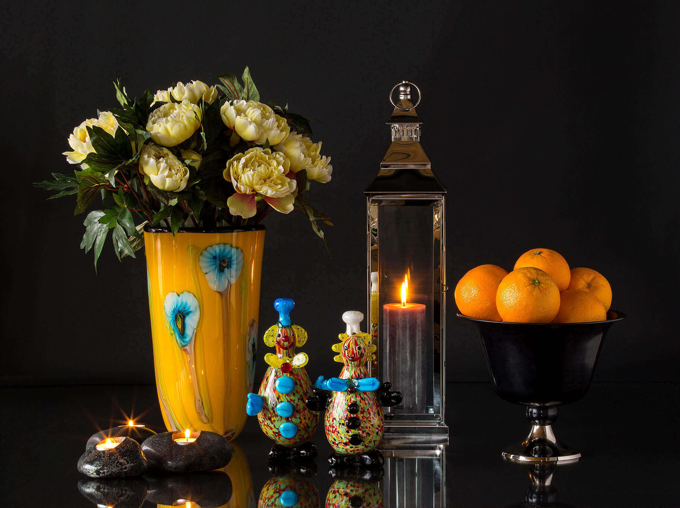 Two clown figurines in glass in front of yellow glass vase, lantern and fruit bowl