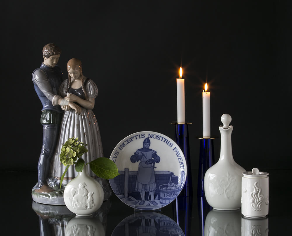 Figurine of Maid and Knight next to a masonic plate and Royal Copenhagen jars