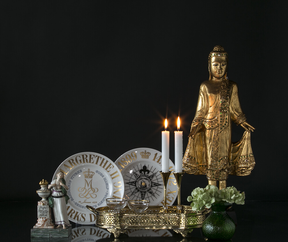 Buddha flanked by memorial plates and friendship figurine behind tray with Asmussen Hexa candlesticks