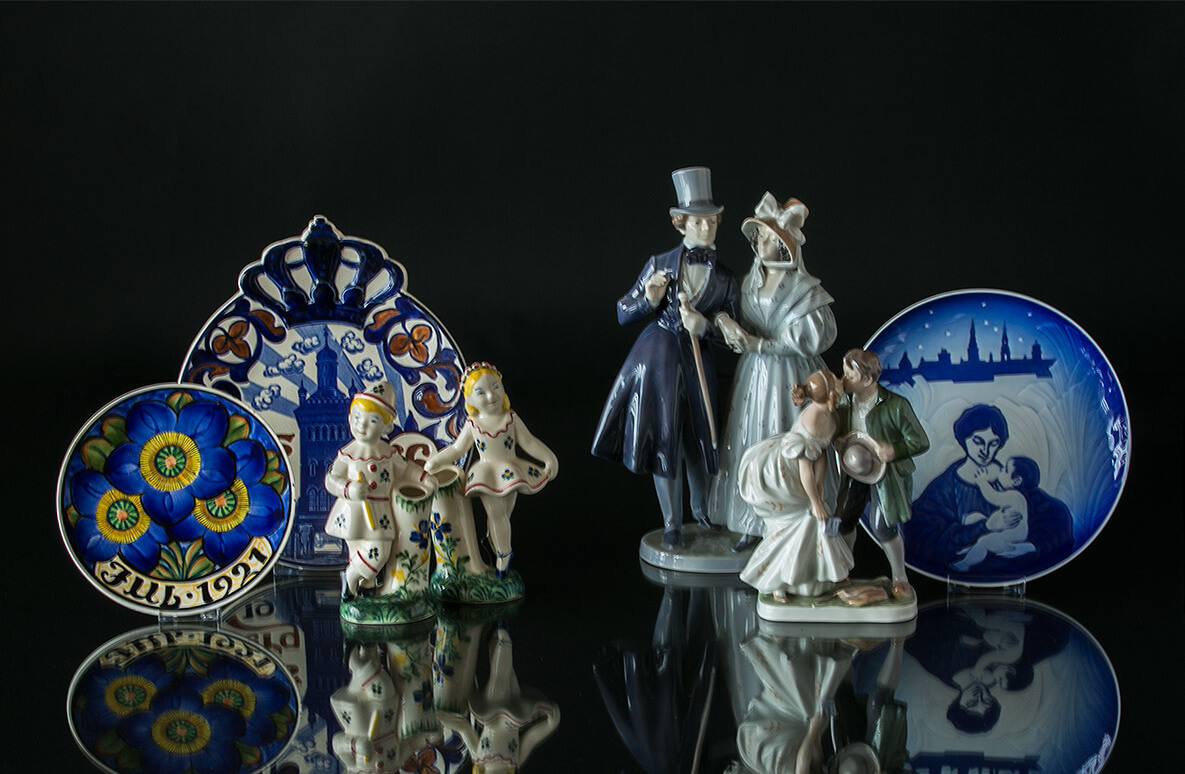 Aluminia Child welfare figurines and plates next to Royal Copenhagen figurines and plate