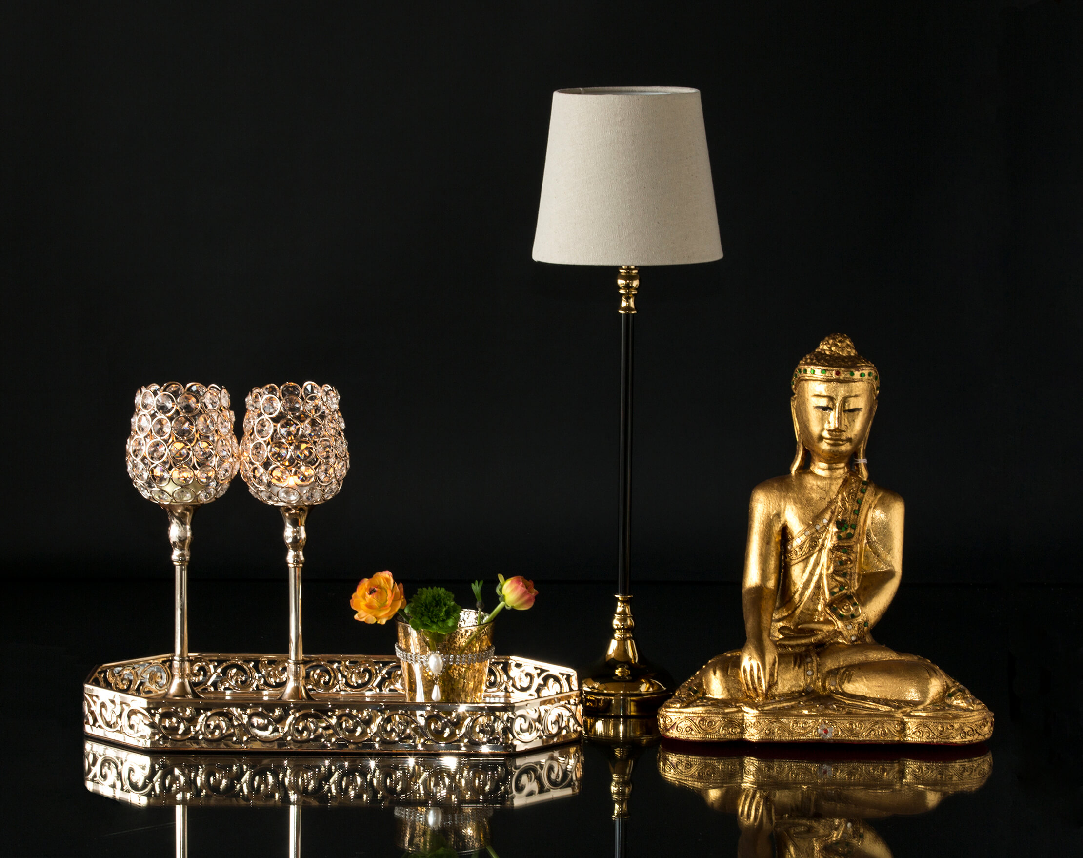 Buddha next to small lamp and mirror tray with candlesticks