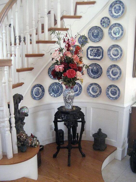 Plates give life as wall decoration on a curved wall by the stairs