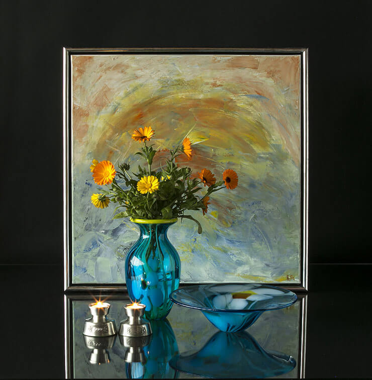Glass vase and bowl with flowers and tin candleholders