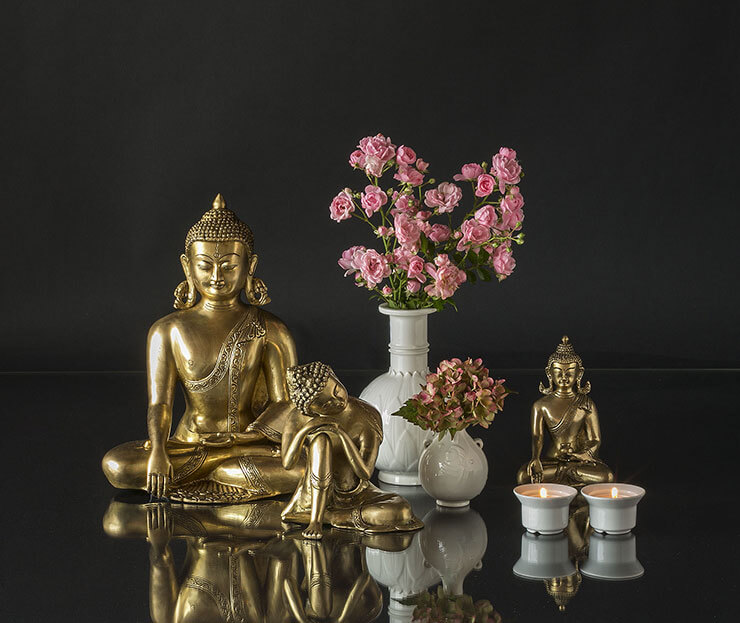 Buddha statues in an arrangement with vases and tealight candleholders