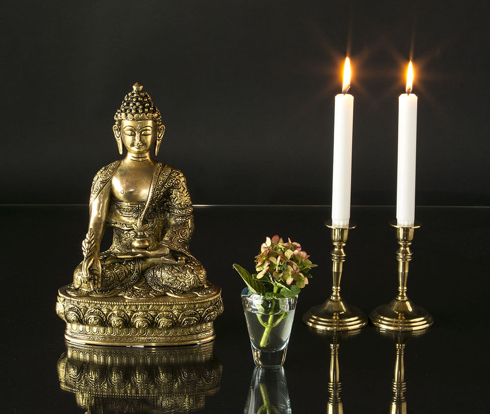 Brass Buddha statue with glass vase with flowers